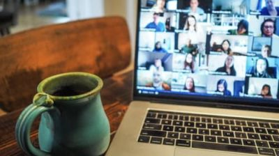 Coffee mug in front of computer screen